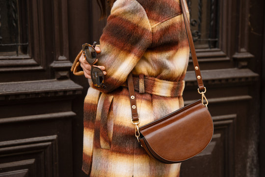 authentic street style portrait of an attractive woman wearing plaid check jacket coat, sunglasses and brown leather bag, crossing the street. fashion outfit details perfect for autumn fall winter