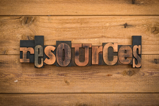 Resources, word written with vintage letterpress printing blocks on rustic wood background