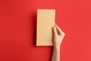 Female hand with blank menu on color background