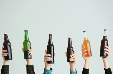 Hands with bottles of beer on grey background