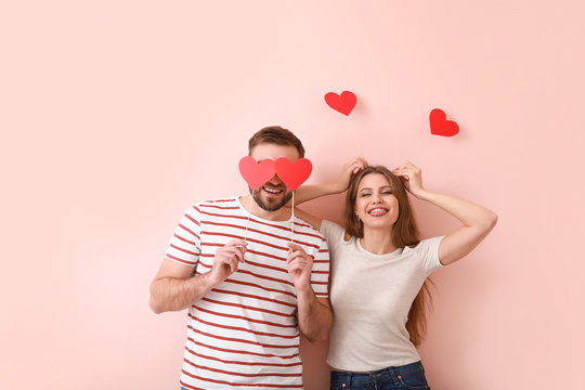 Happy young couple with red hearts on color background. Valentine's Day celebration