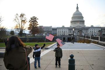 Children holding American flags pose for a photo in front of the U.S. Capitol building on Capitol Hill in Washington