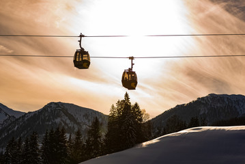 Foto op Canvas Gondolas Ski lift, two gondolas against the backdrop of an orange, cloudy sky. In the background visible mountains covered with snow. Cable car at Schladming Dachstein, Austria.
