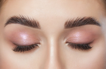 Beautiful young woman with long eyelashes, beautiful fresh nude make-up, thick eyebrows and with clean skin in a beauty salon. Eyelash extensions. Eyebrows close up. Make-up concept.