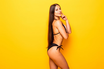 Young sexy slim tanned woman in black swimsuit posing against yellow background.