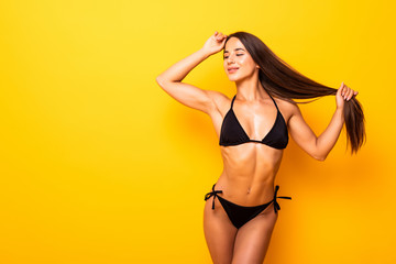 Smiling young woman posing with her black bikini swimsuit on yellow background