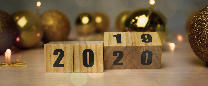 New Year concept from 2019 to 2020. Business and design concept - surreal abstract geometric floating wooden cube with word 2020 2019 concept on wood floor and christmas background