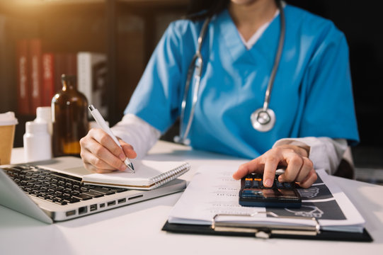 Healthcare costs and fees concept.Hand of smart doctor used a calculator and smartphone, tablet for medical costs at hospital in morning light