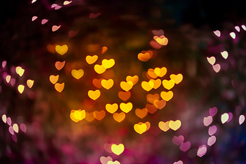 Abstract beautiful blurred gold-yellow orange and red colored of heart bokeh like autumn leaves from ornamental lights flickering in the park. Background for Autumn season, Valentine or Love concept.
