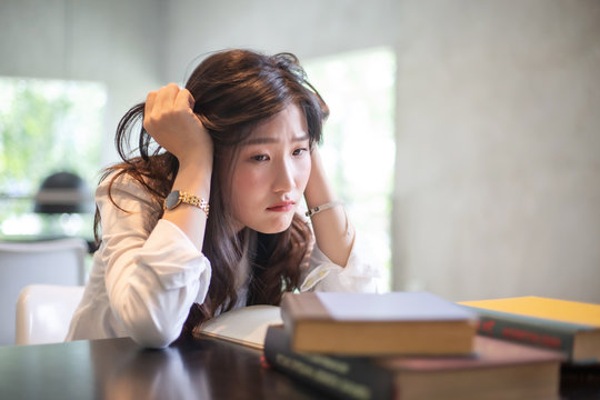 Young Asian girl with stress emotion while reading a lot of books and doing her homework in the university