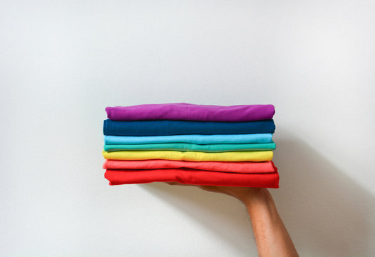 close up stack of folded multicolored t-shirt in hand over white background, copy space