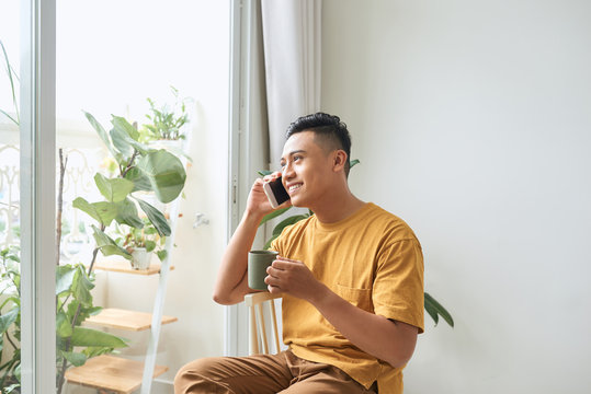 Young man wearing casual clothes talking on a mobile phone in the morning at a window