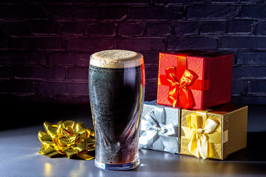 A dark Irish dry stout beer glass with December holidays gift boxes presents