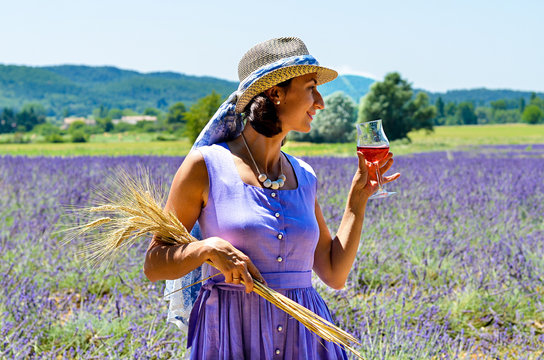 A portrait of a young woman drinking rose wine with a lavender fields as a background. She is wearing a purple dress and a hat