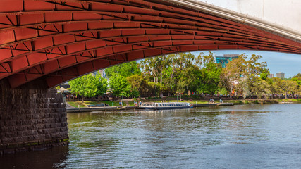 A Melbourne sightseeing boat is docked on the Yarra River framed by Princes Bridge