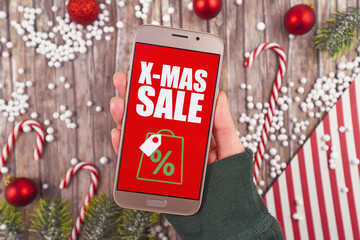 Concept for Christmas seasonal online shopping and sales with hand holding cell phone with red 'X-Mas Sale' sign in front of desk with seasonal decorations like baubles and candy canes