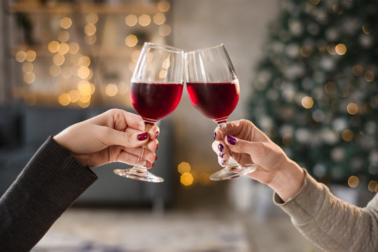 Female hands close up at christmas lights background hold wine glasses