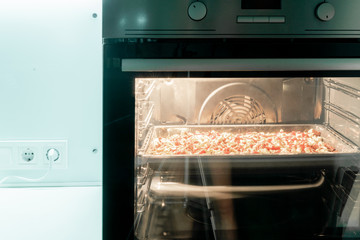 Big rectangular pizza cooks in the built-in electric oven. White kitchen. Culinary. Food. Stove