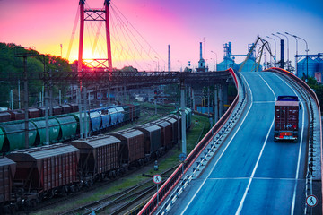 truck with container rides on the road, railroad transportation, freight cars in industrial seaport at sunset Fototapete