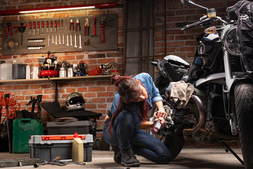 Woman mechanic in garage inspecting motorcycle