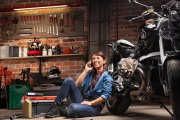 Female biker relaxing alongside her vintage bike