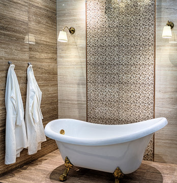 Interior of a modern bathroom with a large white bathtub and travertine tiles