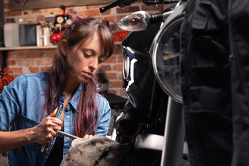 Female mechanic working on a vintage motorbike