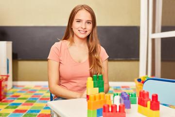 Glückliche Frau als Kindergärtner im Kindergarten