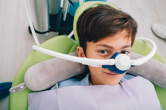 Little boy getting Inhalation Sedation while teeth treatment at dental clinic. Teeth treatment child