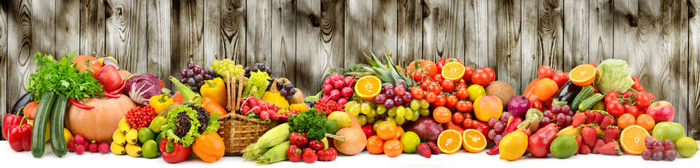 Different ripe fruits and vegetables on dark wooden background for kitchen panel.