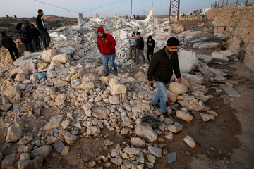 People check the family house of Palestinian assailant Asafra after it was demolished by Israeli forces in the Israeli-occupied West Bank