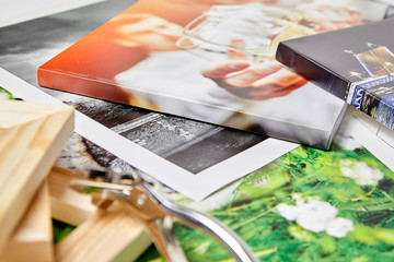 Photo canvas prints. Tool for wrapping. Colorful photographs, pile of wooden stretcher bars and canvas pliers on table. Photos printed on glossy synthetic canvas