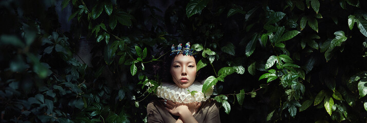 Art portrait of a girl Princess Queen in foliage and greenery, fabulous romantic image of an Asian woman in a magical dress. Sensual gentle glance. The girl in the Palace is waiting for the Prince