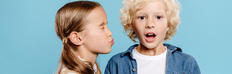 panoramic shot of kid kissing shocked friend isolated on blue
