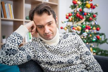Sad man portrait feeling negative emotions during christmas