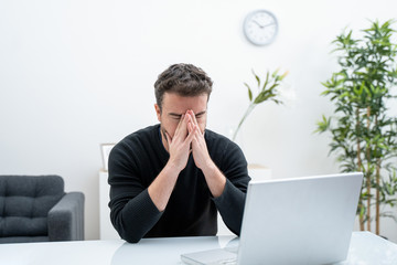 Man feeling bad reading bad news on laptop
