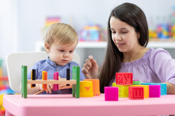 Mother and child toddler playing with educational toys together at home