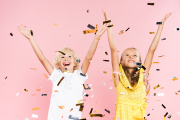 smiling kids with outstretched hands near falling confetti on pink background