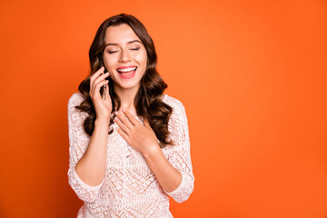 Fototapete - Portrait of cheerful positive girl use cell phone talk with her friend joking laughing wear white blouse isolated over orange color background