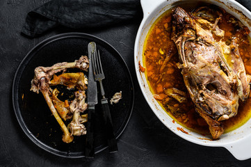A plate of chicken bones and a chicken skeleton in a baking dish. Leftovers from dinner. Black background. Top view