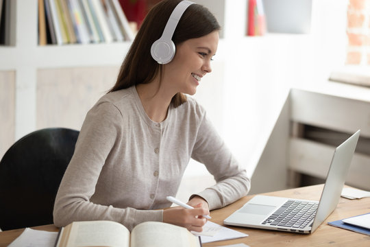 Smiling young female student wearing headset watching educational video.