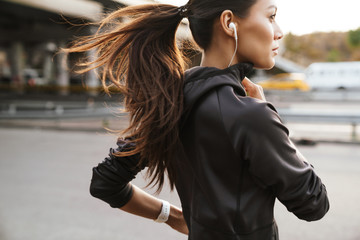 Strong fitness woman running outdoors by street. Fotomurales