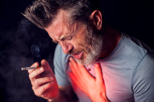 Man smokes cigarette and has problem with lungs. Cigarette addiction concept