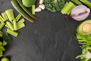 food, culinary and healthy eating concept - close up of different green vegetables and fruits on...