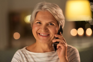 technology, communication and people concept - happy smiling senior woman calling on smartphone at home in evening