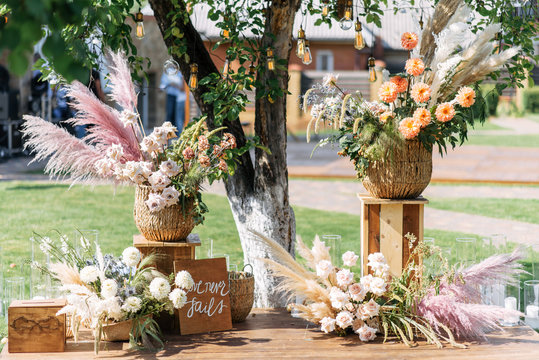 Outdoor wedding ceremony. Composition of chrysanthemums, pampas grass and roses