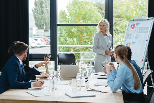 smiling businesswoman standing near flipchart during business meeting with young colleagues