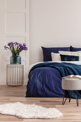 Purple flowers in blue glass vase on stylish bedside table next to king size bed