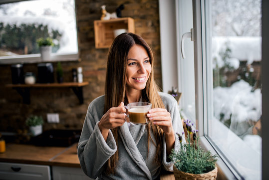 Beautiful smiling brunette looking through window and drinking coffee in the kitchen.