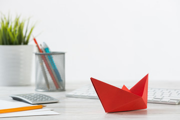 Wooden office desk with red origami boat